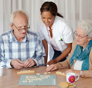 A senior couple and care assistant playing a board game togetherの写真素材 [FYI02693423]