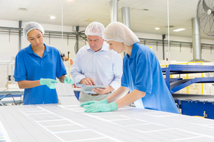 Businessman and technicians arranging solar cells to form solar panel on production lineの写真素材 [FYI02693466]