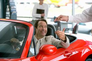 Salesman handing man keys to new red convertibleの写真素材 [FYI02693476]