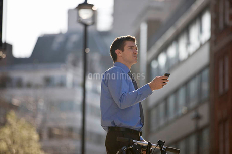 A businessman checking directions using his mobile phoneの写真素材 [FYI02693496]