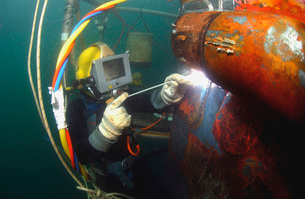 U.S. Navy Diver welds a repair patch on the submerged bow ofの写真素材 [FYI02693507]