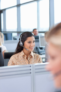 Brunette businesswoman wearing headset in officeの写真素材 [FYI02693512]