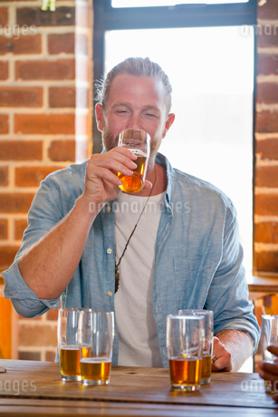 Drunk Male Customer Standing At Bar Counter Drinking Beerの写真素材 [FYI02693559]