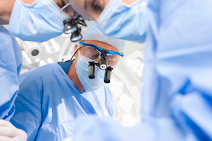 Concentrating surgeons performing operation in operating roomの写真素材 [FYI02693566]