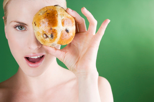 A young woman holding a hot cross bun in front of her eyeの写真素材 [FYI02693568]