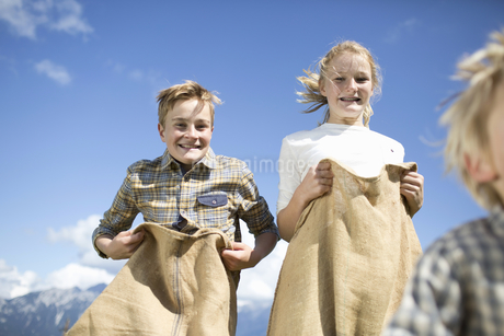 Teenage Children Having Sack Race In Countrysideの写真素材 [FYI02693600]