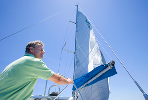Man in green polo shirt standing at helm of sailing boat, steering, rear view, low angle viewの写真素材 [FYI02693613]