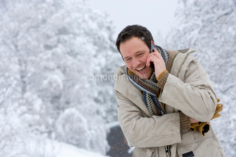 Mid adult man on the phone outdoors in snowの写真素材 [FYI02693633]