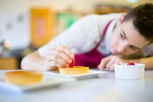 Focused male high school student plating dessert in home economics classの写真素材 [FYI02693641]