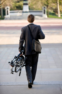 A businessman carrying his folded bicycle to workの写真素材 [FYI02693667]