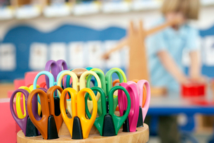 Boy (4-6) standing in classroom, focus on multi-coloured scissors in pot in foregroundの写真素材 [FYI02693677]