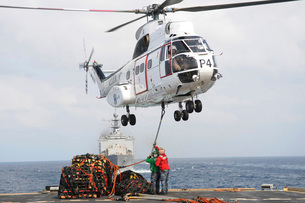 Sailors hook up a pole pendant to a SA-330J Puma helicopter.の写真素材 [FYI02693683]