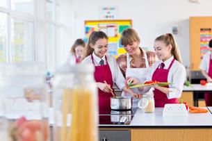 Teacher guiding high school students cooking in home economics classの写真素材 [FYI02693685]