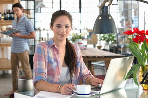 Portrait of smiling woman with coffee and laptop at kitchen tableの写真素材 [FYI02693689]