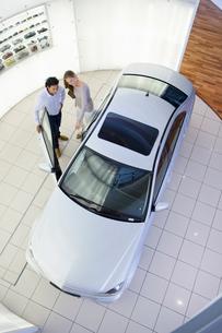 Couple looking inside car in car dealership showroomの写真素材 [FYI02693703]