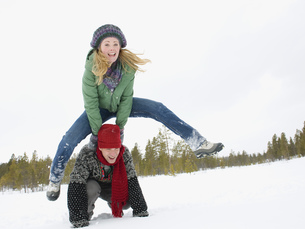 A young couple playing leap frog in the snowの写真素材 [FYI02693726]