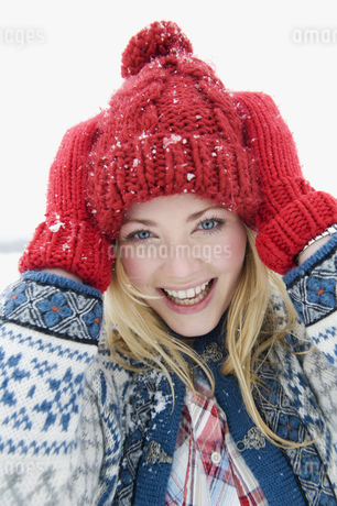 A portrait of a young woman wearing a red woolen hat and glovesの写真素材 [FYI02693758]