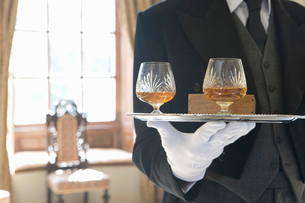 Butler with tray of drinks, mid sectionの写真素材 [FYI02693781]