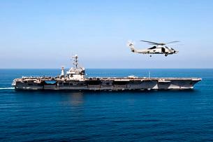 An MH-60R Sea Hawk flies near the Nimitz-class aircraft carrの写真素材 [FYI02693791]