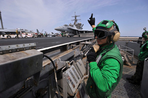 Aviation Boatswain's Mate signals to a shooter as an F/A-18E Supの写真素材 [FYI02693840]