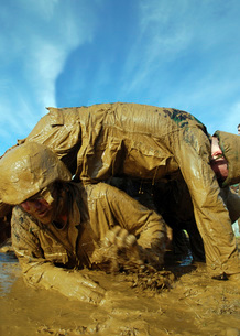 A midshipman crawls through fellow plebes in an obstacle course.の写真素材 [FYI02693845]