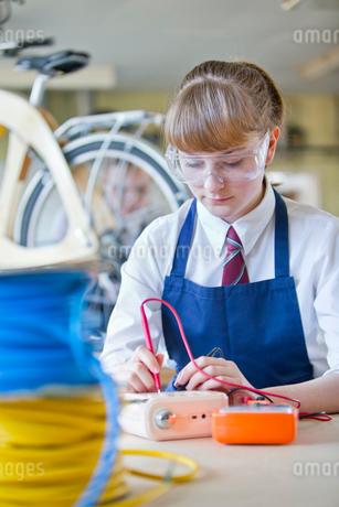 Female high school student testing electronics in shop classの写真素材 [FYI02693849]