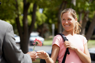 Woman receiving single pink flower from man, smilingの写真素材 [FYI02693854]