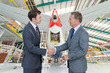 Businessmen Shaking Hands In Aircraft Maintenance Hangarの写真素材 [FYI02693921]