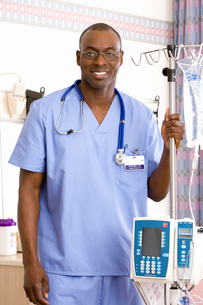 Young male doctor holding IV stand, smiling, portraitの写真素材 [FYI02693984]