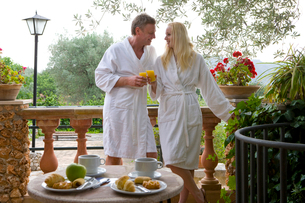 Couple in bathrobes eating breakfast and toasting orange juice glasses on patioの写真素材 [FYI02694009]