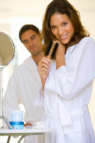 Young couple in bathrobes, woman with hairbrush, smiling, portrait (differential focus)の写真素材 [FYI02694017]