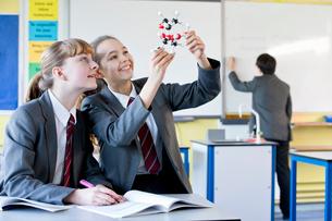 Smiling high school students examining molecule model in science classの写真素材 [FYI02694050]