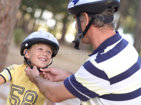 Father adjusting strap of son's (8-10) cycling helmet, smiling (tilt)の写真素材 [FYI02694058]