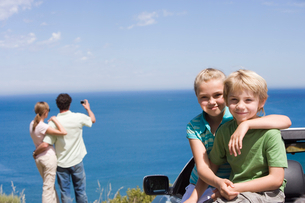 Parents photographing Atlantic Ocean from clifftop, focus on children (6-9) sitting in parked converの写真素材 [FYI02694060]