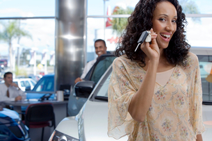 Salesman and customer in car showroom, focus on woman holding key beside new car, smiling, portraitの写真素材 [FYI02694075]
