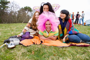 Laughing friends in silly costumes attending outdoor festivalの写真素材 [FYI02694076]