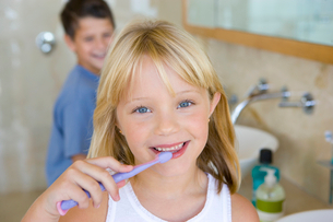 Boy and girl (6-8) brushing their teeth in bathroom, smiling, portrait, girl in foregroundの写真素材 [FYI02694079]