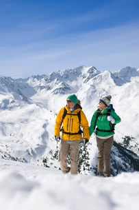 Happy couple holding hands and backpacking on snowy mountainの写真素材 [FYI02694081]