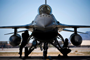 U.S. Air Force crew chiefs do pre-flight checks under an F-16 Fighting Falcon.の写真素材 [FYI02694127]