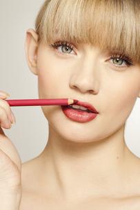 Portrait of young woman applying lip linerの写真素材 [FYI02694130]