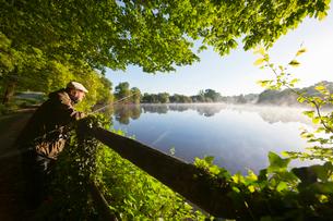 Fisherman carp fishing at dawn at fence along tranquil misty lakeの写真素材 [FYI02694135]