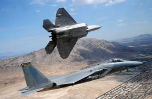 An F-22 Raptor aircraft turns away while an F-15 Eagle fliesの写真素材 [FYI02694139]