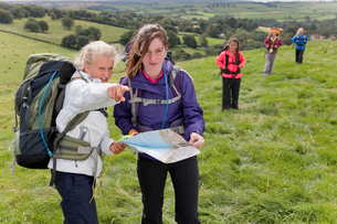 Girls with backpacks compass and map pointing in fieldの写真素材 [FYI02694144]
