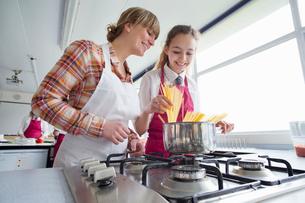Teacher teaching high school student cooking pasta in home economics classの写真素材 [FYI02694184]