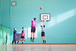 Gym teacher teaching high school students playing basketball in gym classの写真素材 [FYI02694189]