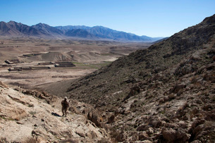 U.S. Marine climbs a hill to conduct a site survey in Afghanの写真素材 [FYI02694217]