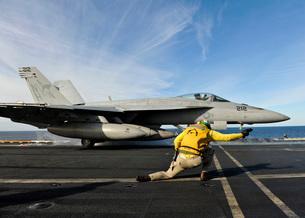 A shooter signals to launch an F/A-18E Super Hornet aboard USS Nimitz.の写真素材 [FYI02694325]