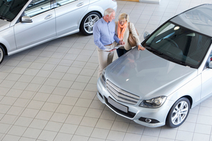 Couple with brochure looking at car in car dealership showroomの写真素材 [FYI02694413]