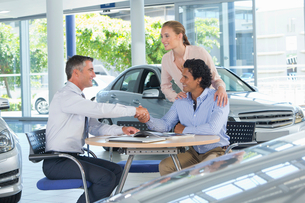 Salesman and couple shaking hands at table in car dealership showroomの写真素材 [FYI02694429]