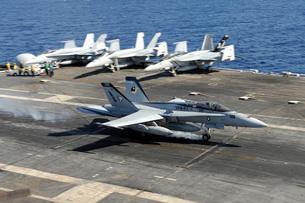 An F/A-18E Super Hornet lands aboard the aircraft carrier USS Dwight D. Eisenhower.の写真素材 [FYI02694534]